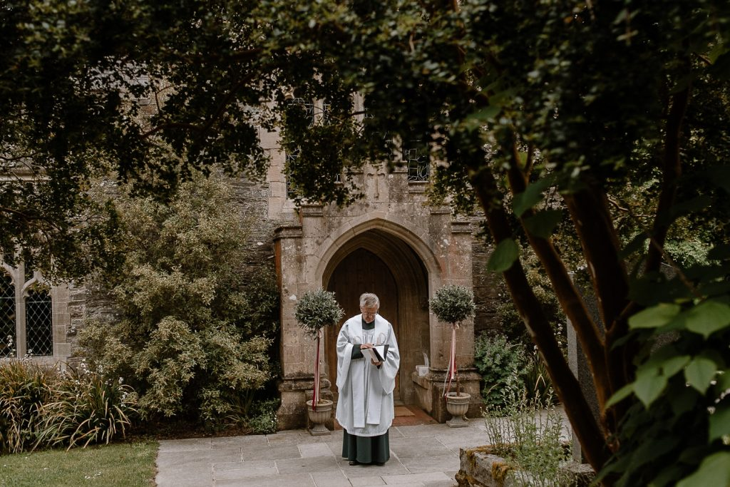 Priest standing outside chapel waiting for the bride