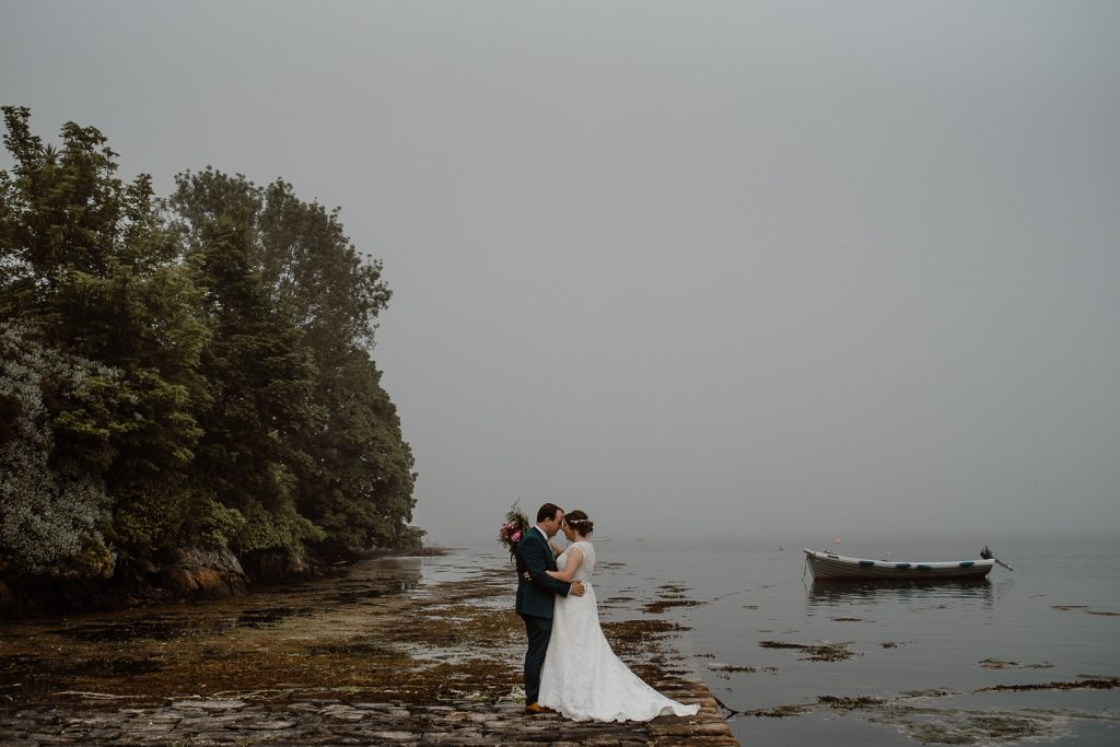 bride and groom in misty landscape by water with small boat