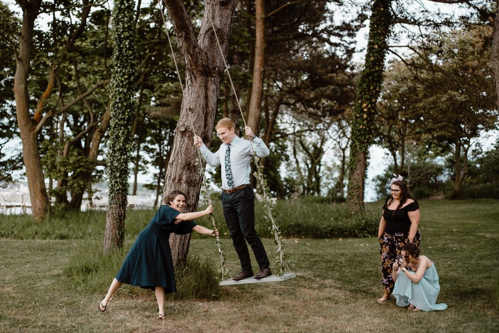 guests play on a swing at old court chapel wedding
