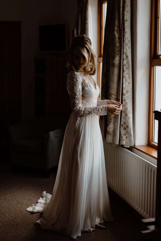 bride at window on wedding day in her dress.