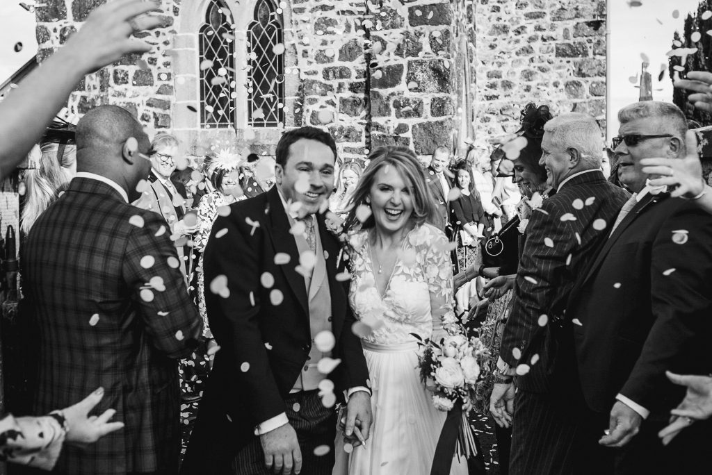 The ivory Pravillion wedding. bride and groom smiling walking through lots of confetti
