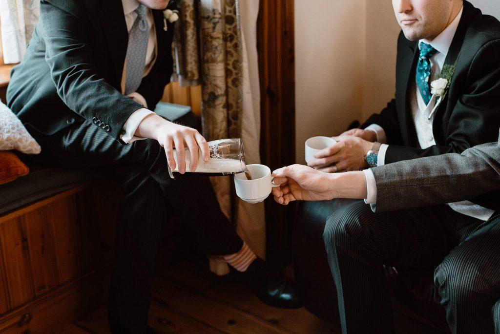 groomsmen pouring beer into tea cup.