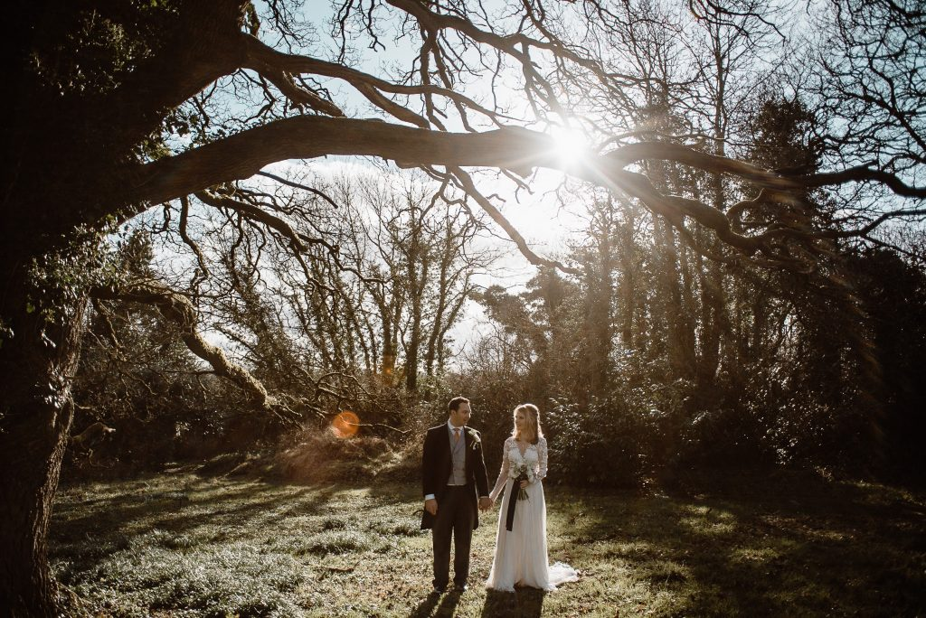 Old court chapel wedding. bride and groom stand together holding hands under big tree branches