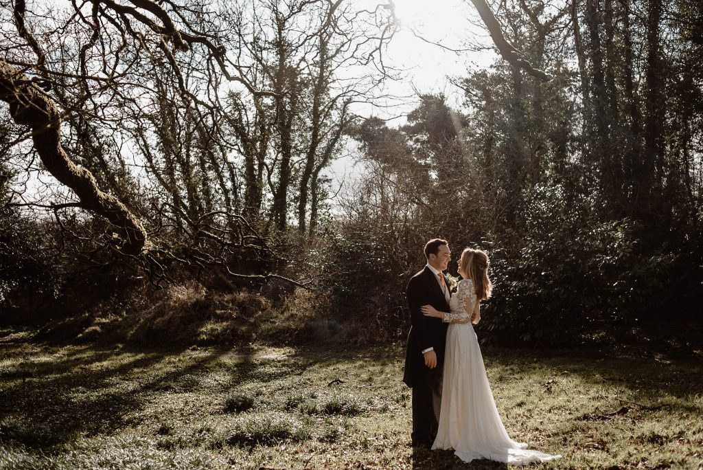 bride and groom standing in grass and beautiful light behind them