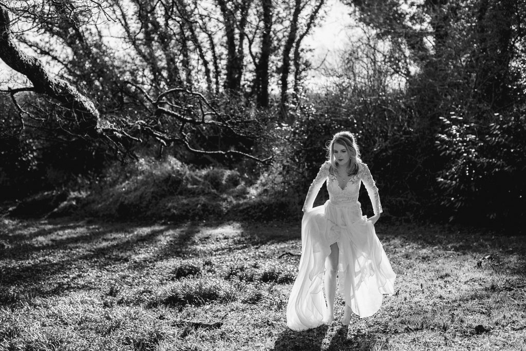 bride lifting dress to walk though a field