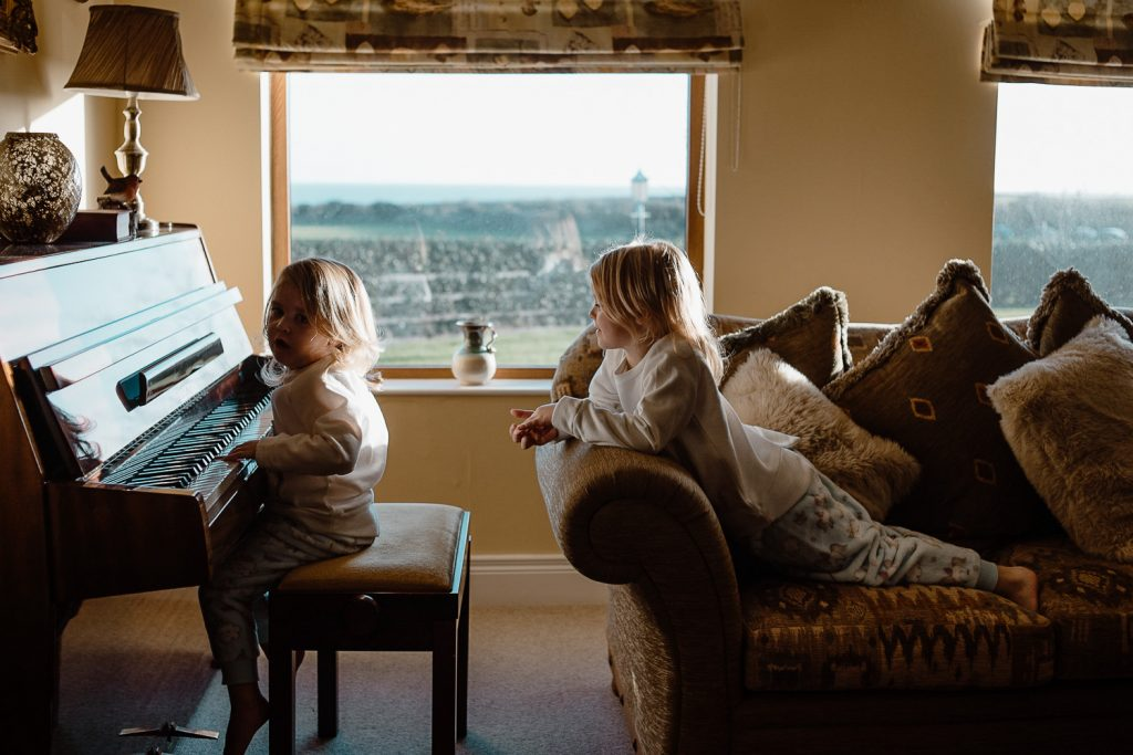 two little girls play piano in their pjs