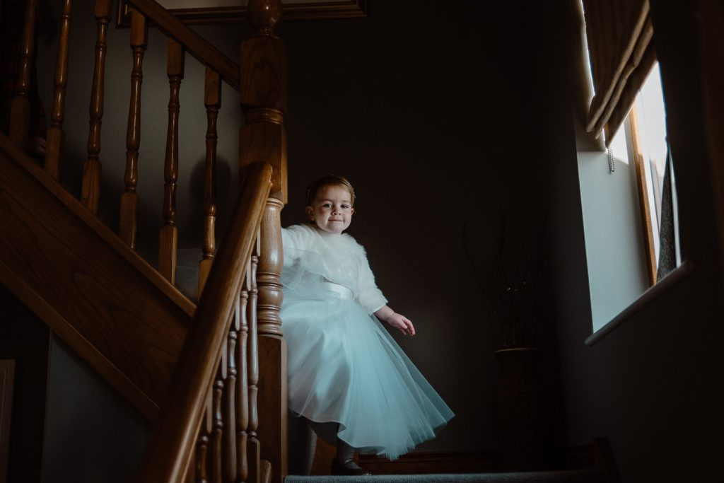 little flower girl going down the stairs