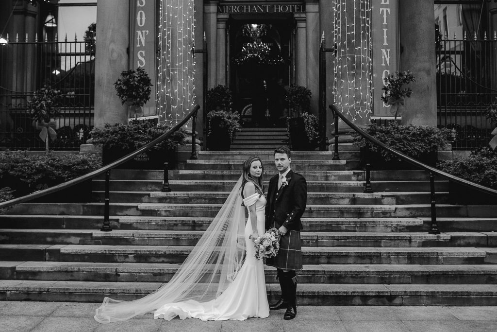 bride and groom standing on the steps of the merchant hotel wedding