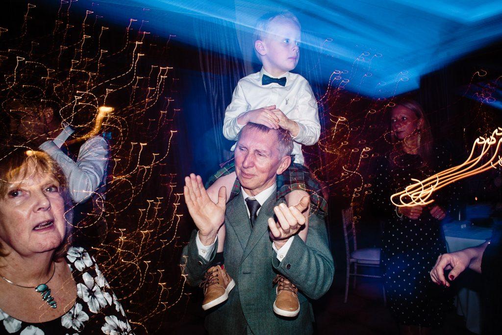 little boy on dads shoulders dancing