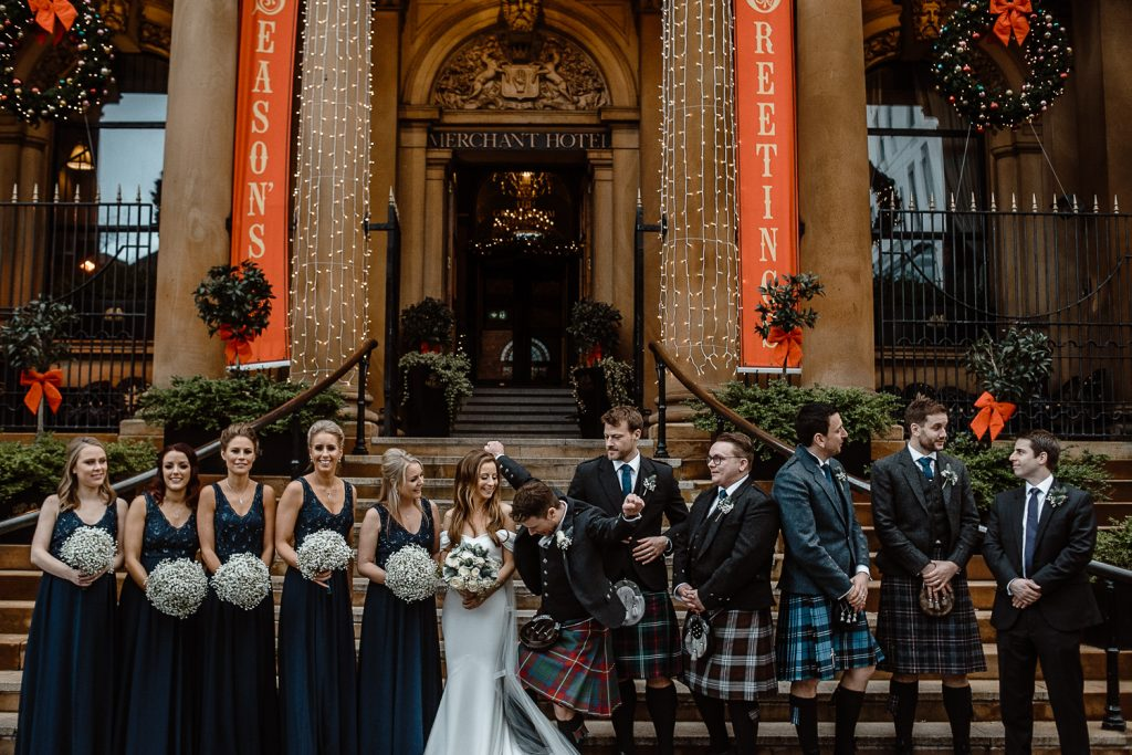 happy bridal party on the steps of the merchant hotel belfast wedding