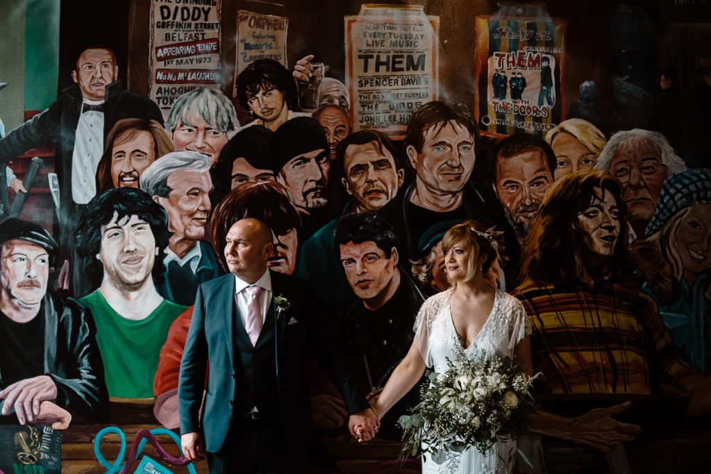 The merchant wedding. bride and groom portrait in front of a wall mural of faces