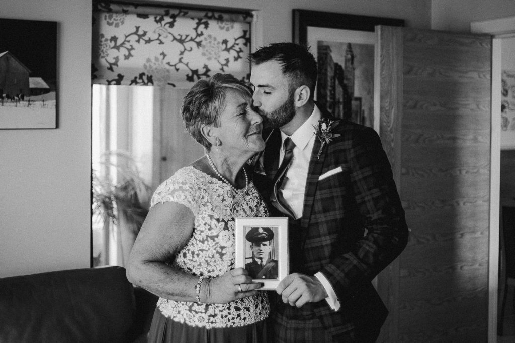Groom kissing grandmother on the head while holding a photograph of his late grandfather.