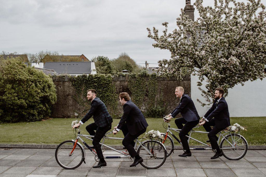 groom and groomsmen on tandem bikes laughing