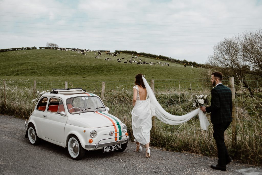 Tullyverry house wedding. bride and groom walking to retro fiat 500 car