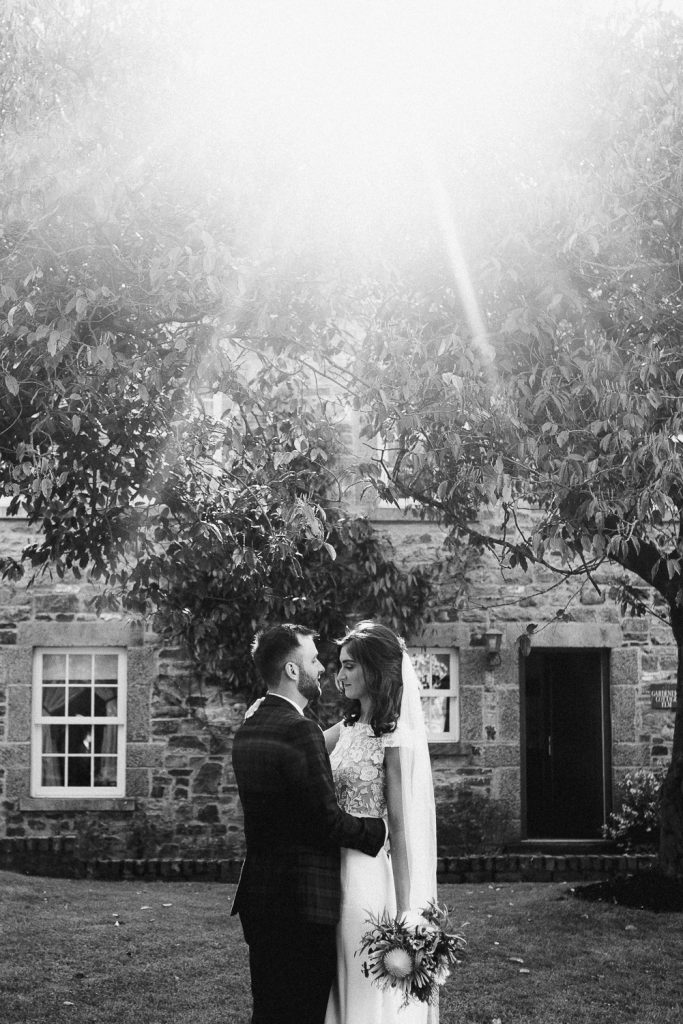 bride and good together under tree and sun rays