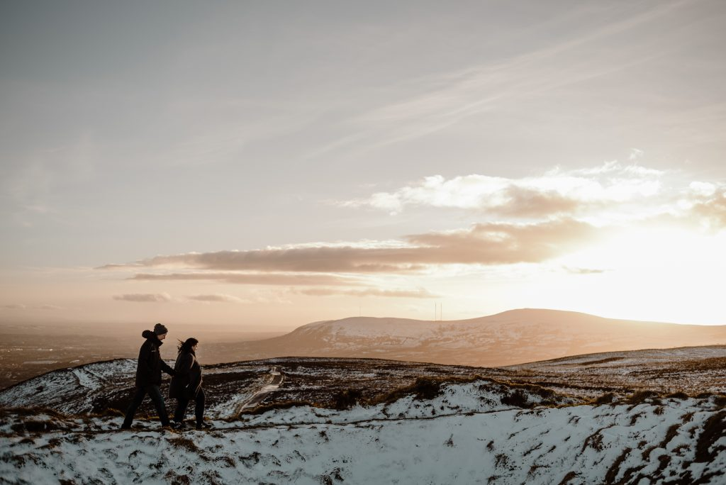 couple walking in snow at sunset on cave hill belfast