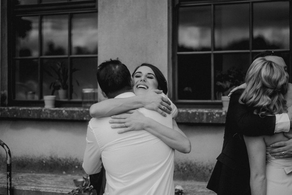 happy bride hugging guest
