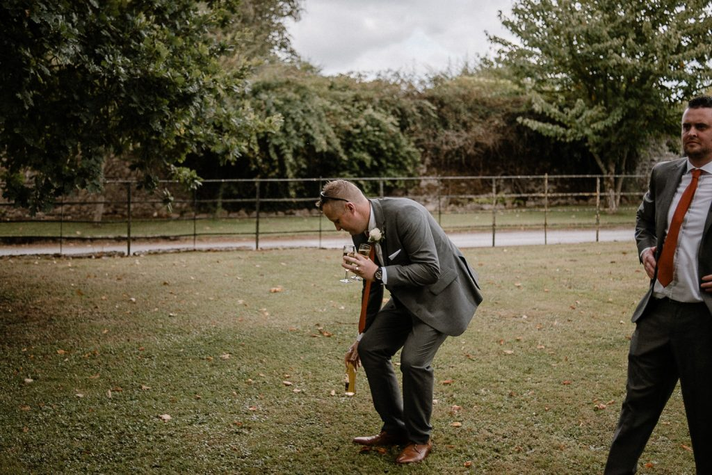 groomsmen setting drinks down on grass before photo