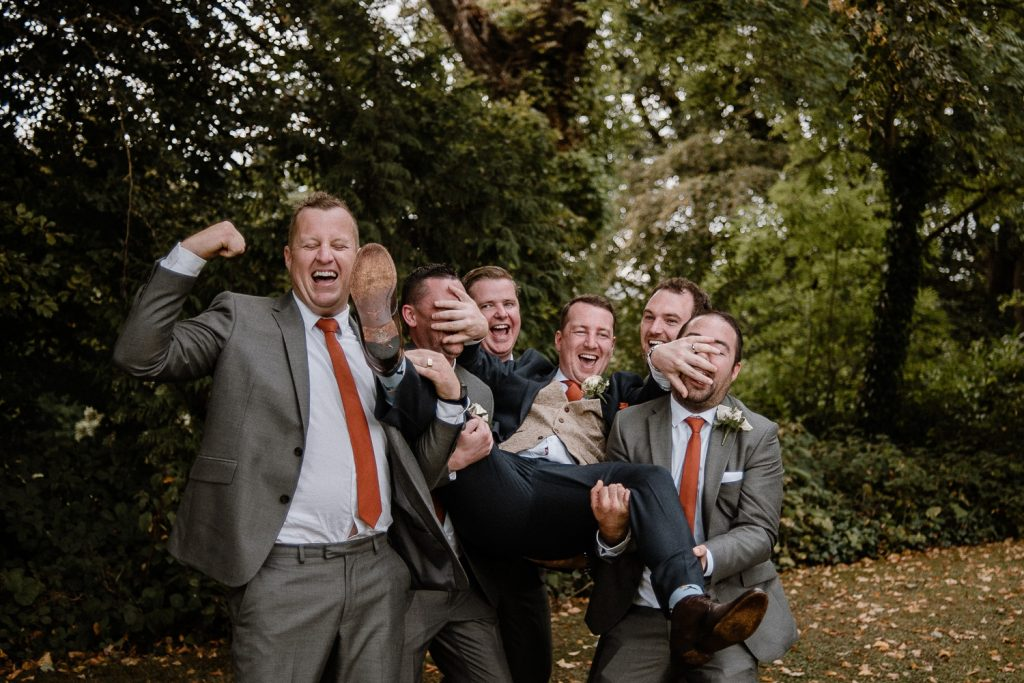 groomsmen lift groom off his feet and  carry him laughing