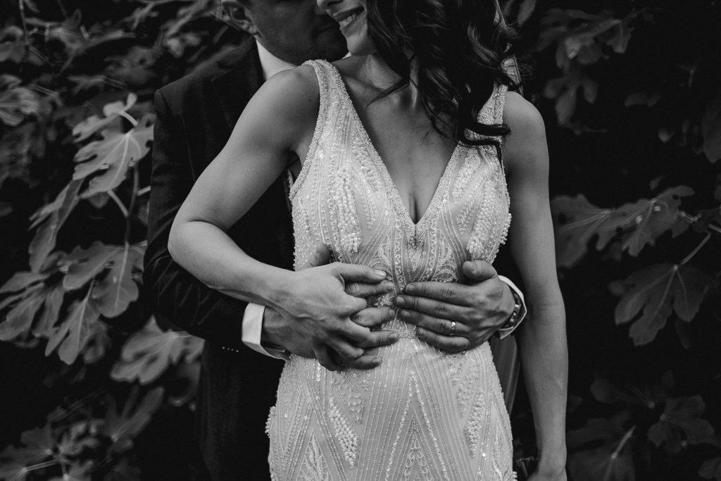 close up of grooms hands around brides waist