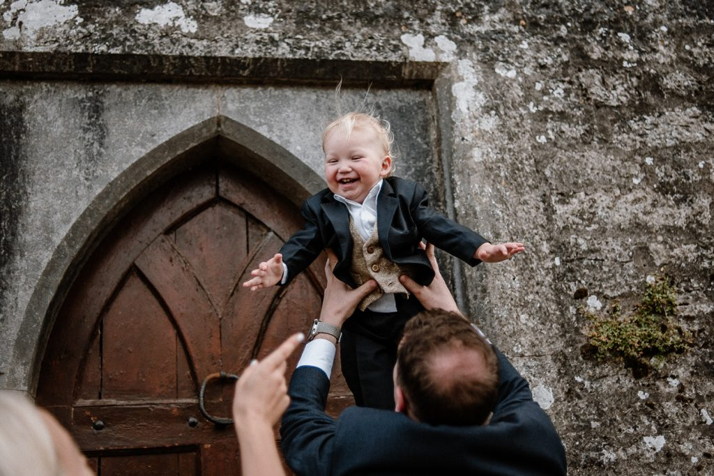 little boy laughs as dad throws him in the air