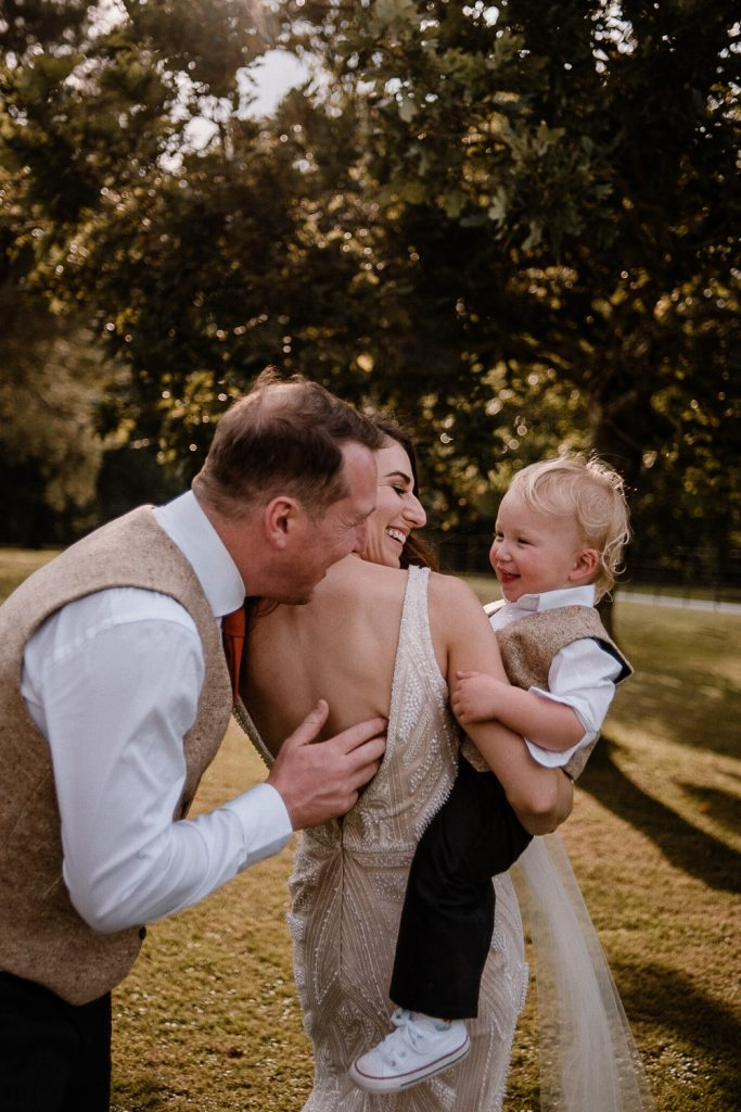 bride and groom playing with their son and laughing together