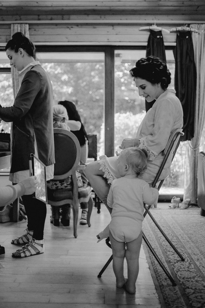 baby boy standing beside mother as she gets make-up applied.