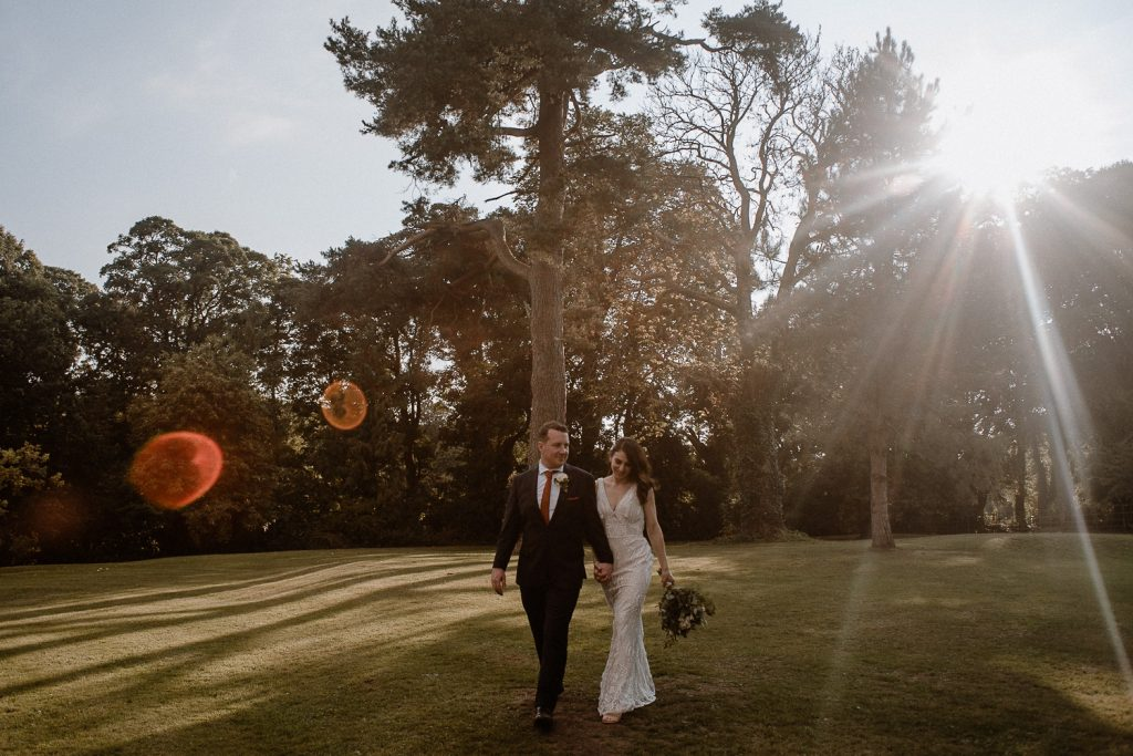 bride and groom walking towards camera with beautiful sun rays