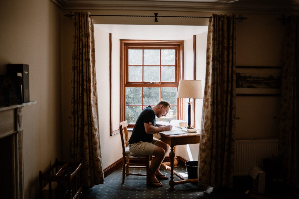 groom sitting at desk writing wedding speech.