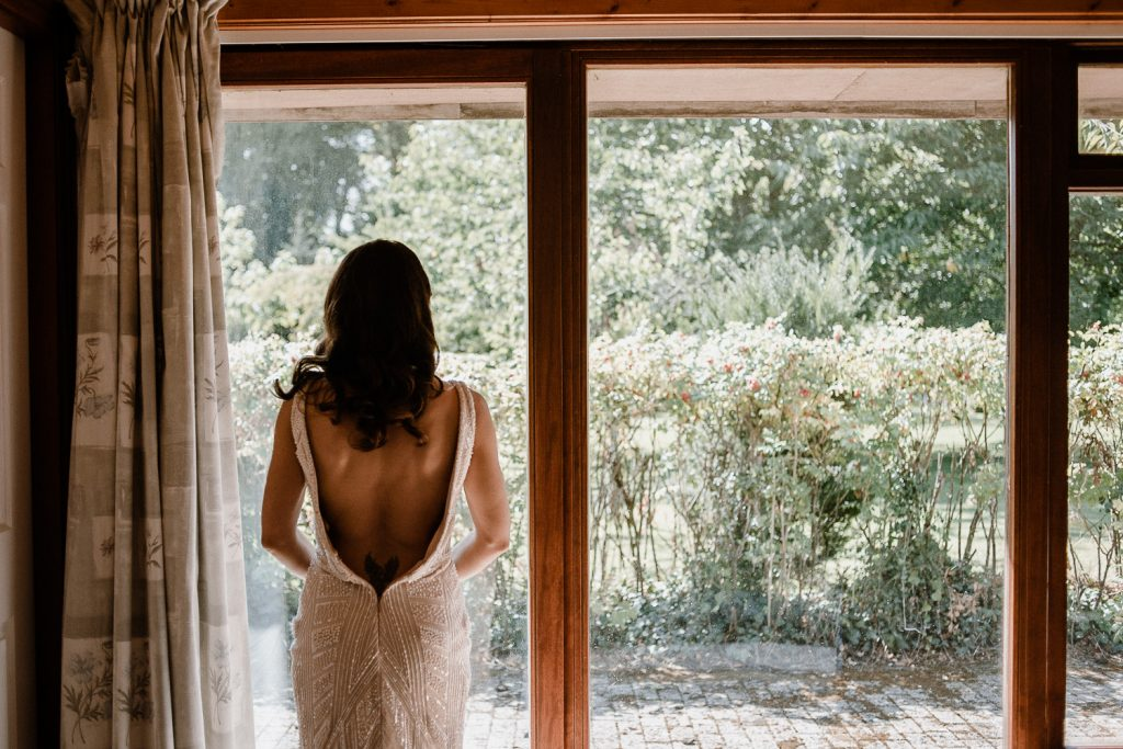bride standing at window looking out.