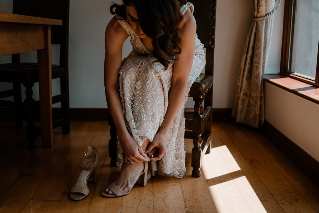 bride fastening shoes on chair by soft window light.