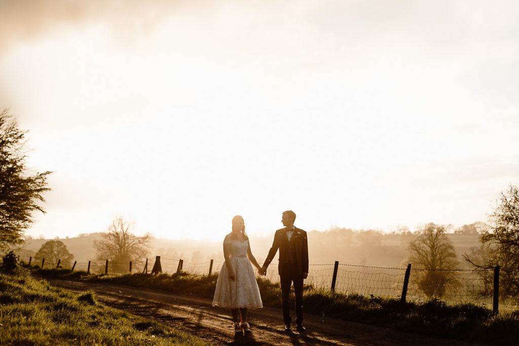 bride and groom standing holding hands at sunset