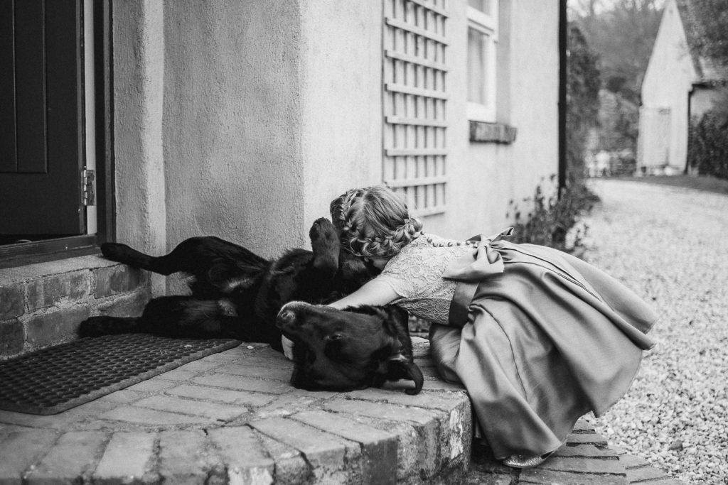 little bridesmaid hugging black dog.