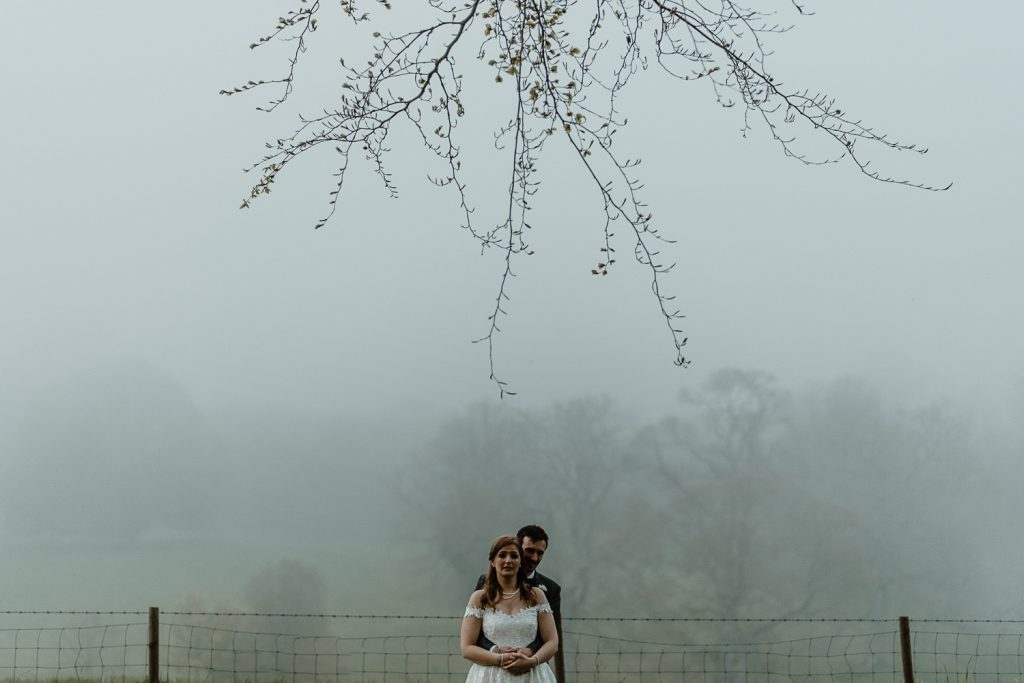 bride and groom surrounded by mist with tree silhouette