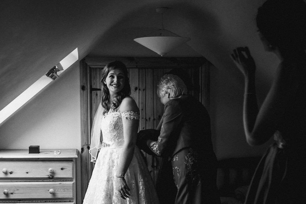 Bride smiling as her mother ties her dress.