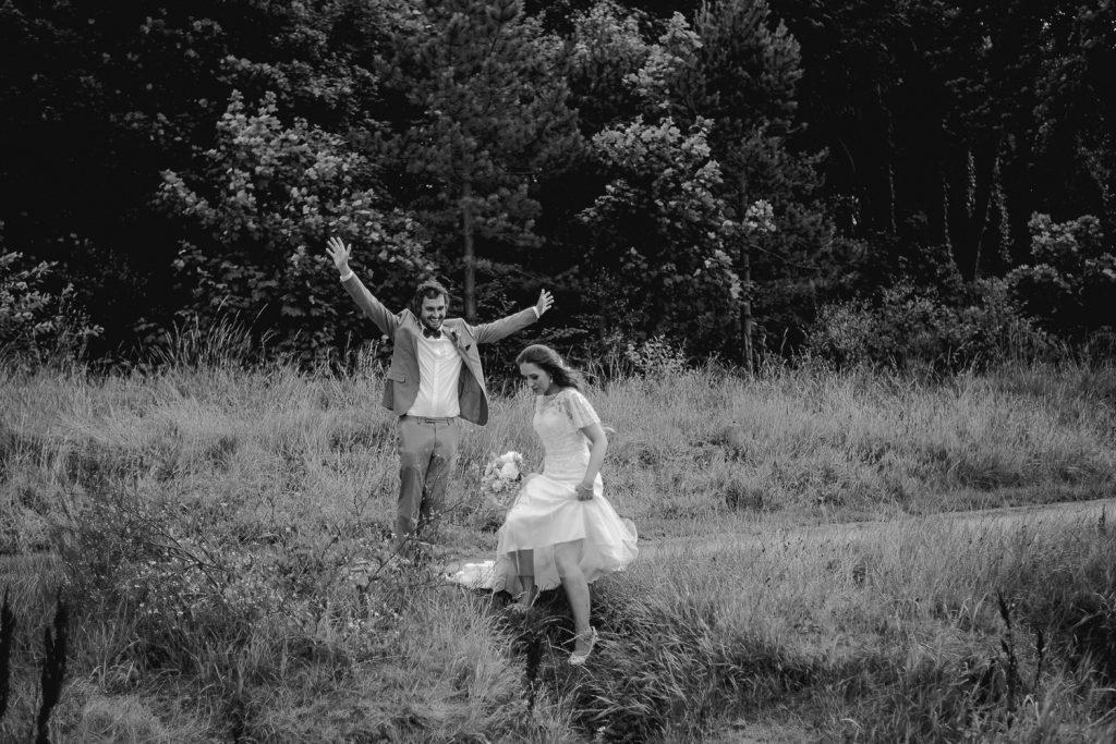 groom with hands in air as bride walks ahead