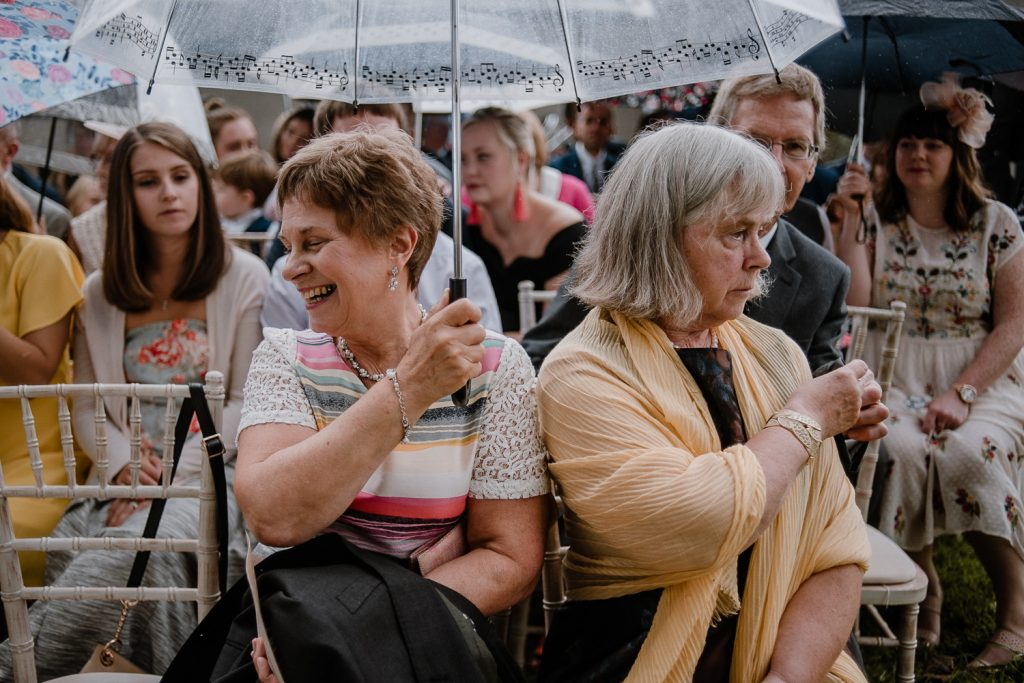 guests at wedding taking shelter under umbrella