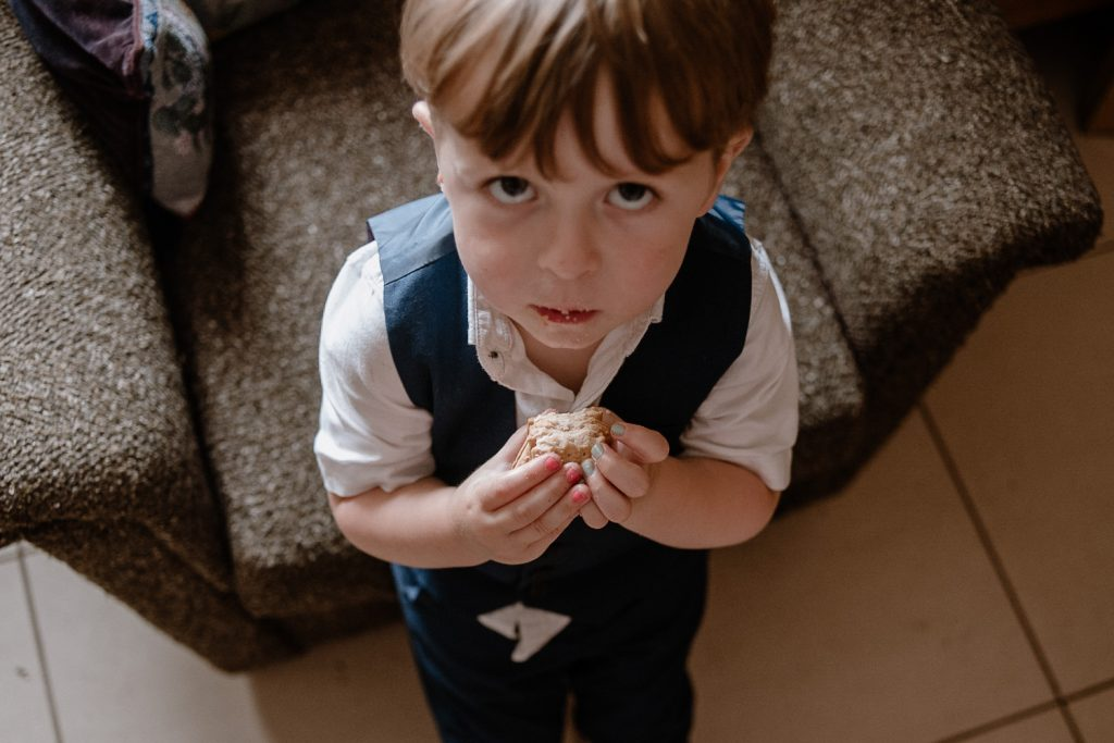 little boy eating sandwich with painted nails