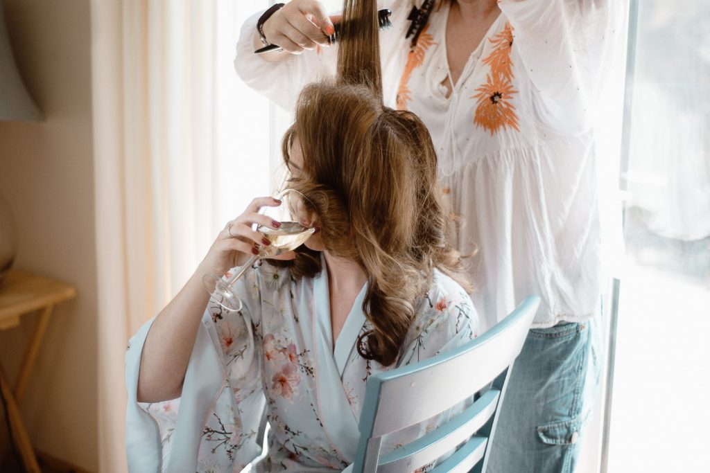 bride drinking champagne on the morning of her wedding.
