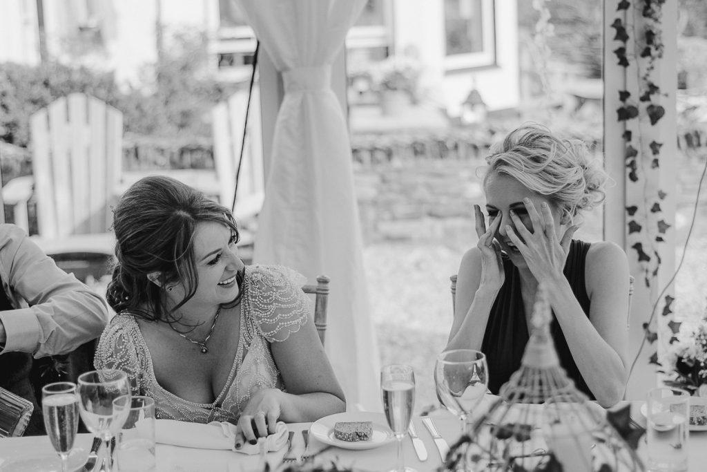 bride and bridesmaid laugh during speeches