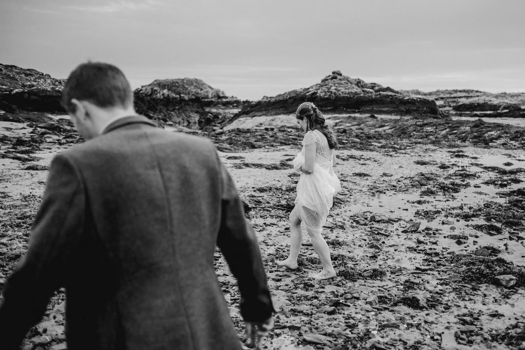 bride walking barefoot, holding dress up on rocky beach
