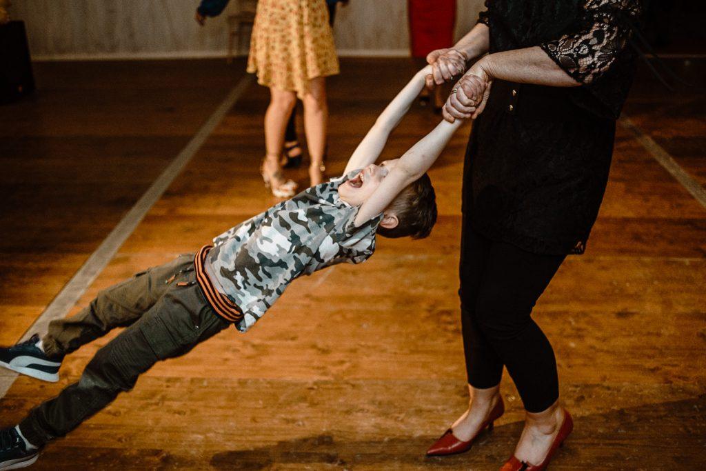 little boy being swung around dance floor