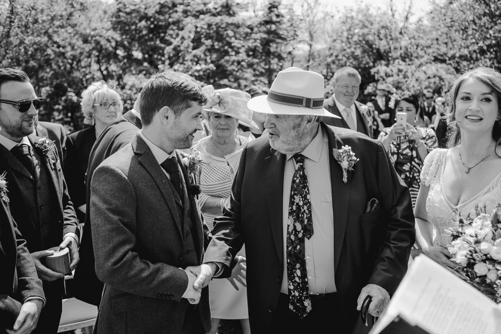 Groom shaking hand of father of the bride as he gives her away