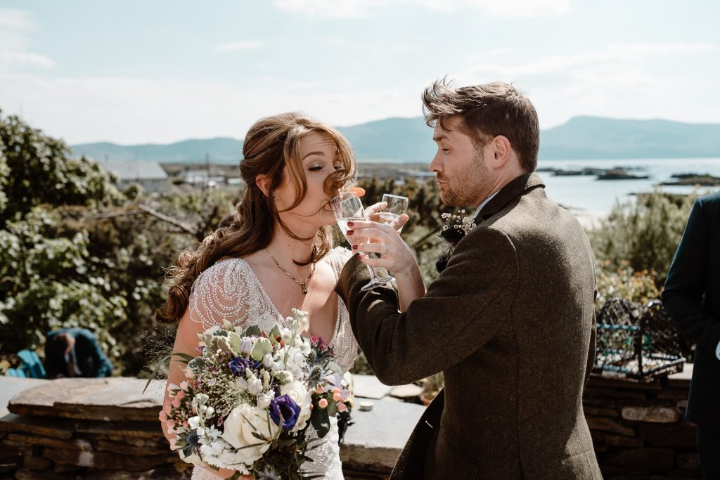 bride and groom drinking together, brides hair is in mouth