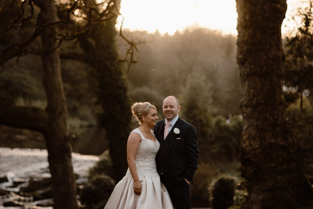 bride looking at groom in forest with soft sunlight