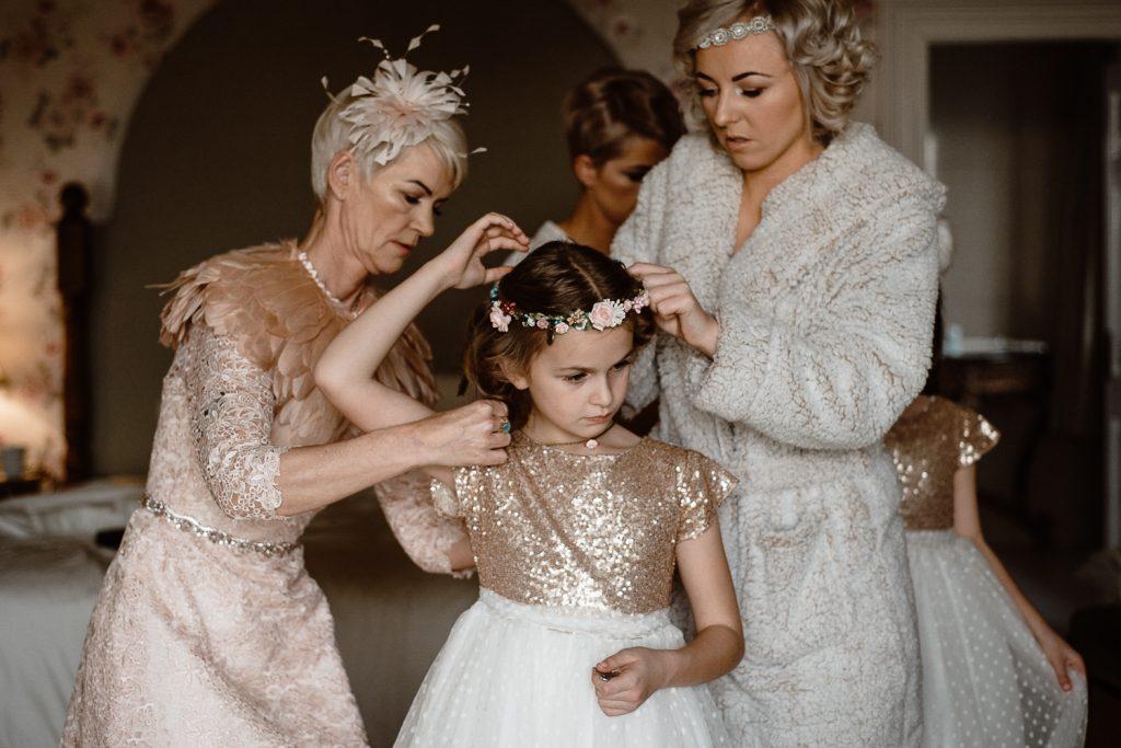 bridesmaid fixing flower girls dress