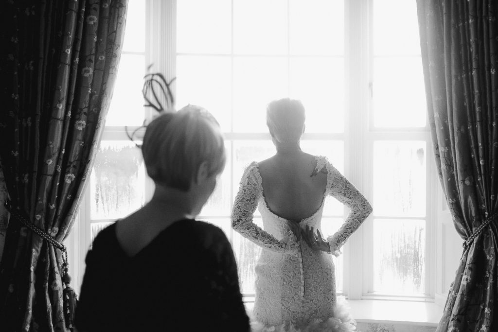 bride fixing back of her dress