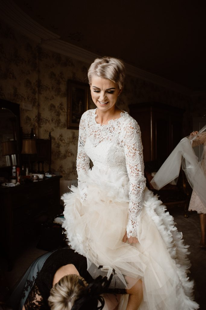 bride holding her dress up as she's are tied