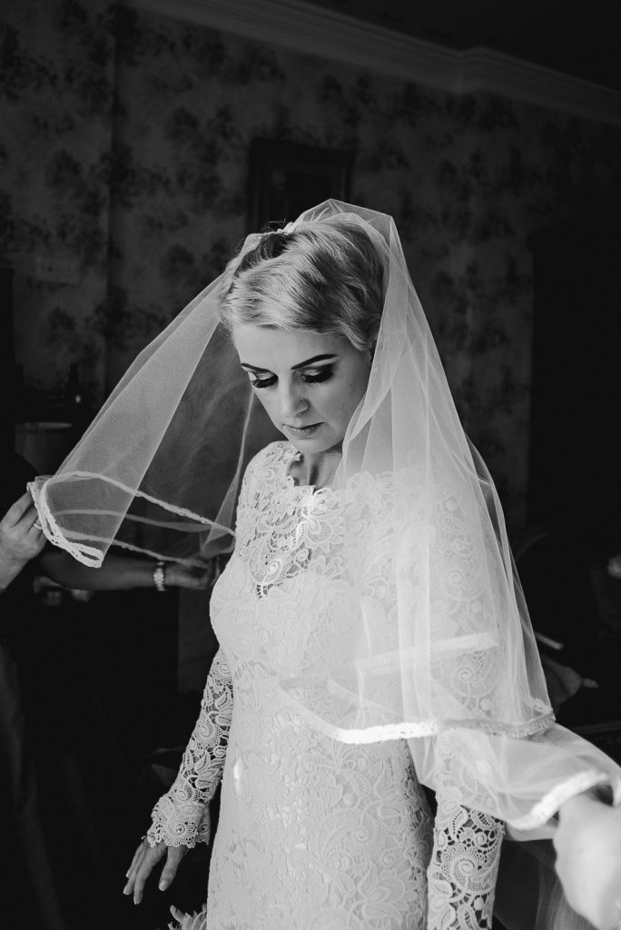bride looking down as vile is fixed