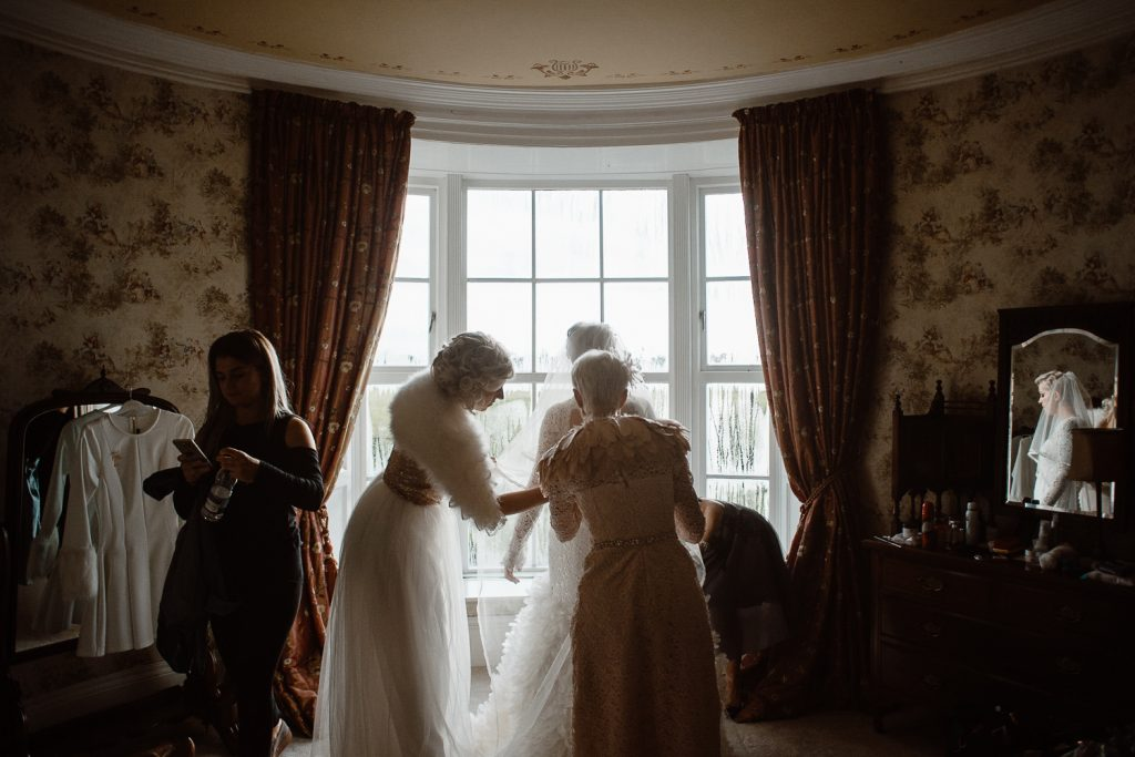 bridesmaids fixing brides dress at window in Gracehall